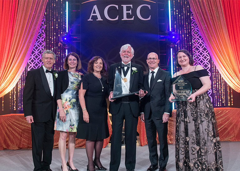 Project staff pose in front of ACEC sign while holding awards, all wearing formal attire