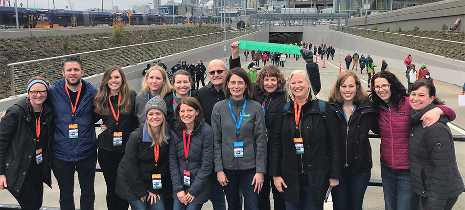 Project staff pose for a picture in front of the Alaskan Way Viaduct tunnel opening